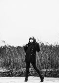 image of cold-weather  - Fashion woman wearing a winter coat and fur cap and she posing front of the reeds cold rainy weather full length black and white image - JPG