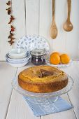 pic of sponge-cake  - Homemade orange sponge cake on a glass cake stand over the kitchen table - JPG