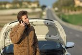 stock photo of angry  - Angry man calling roadside assistance for his breakdown car in a road in winter