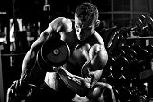 foto of execution  - very power athletic guy bodybuilder execute exercise with dumbbells in dark gym black and white photo - JPG