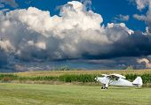 stock photo of cumulus-clouds  - Small white microlight plane ready for take off on a rural field with corn fields alongside under a dramatic cumulus cloud formation - JPG