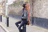 pic of bollard  - A young woman is sitting on a bollard in the street - JPG