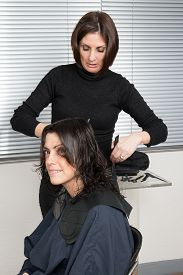 foto of split ends  - Stylist cutting split ends on her client at the salon - JPG