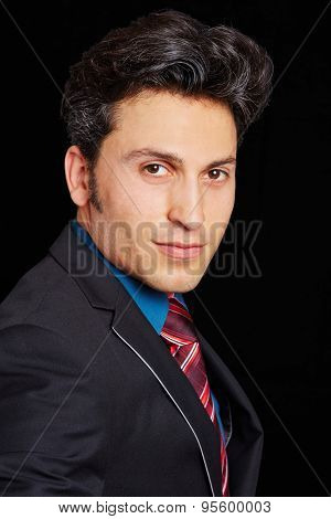 Head shot of successful young businessman on black background