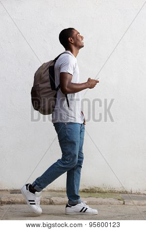 Smiling Male College Student Walking With Bag And Mobile Phone