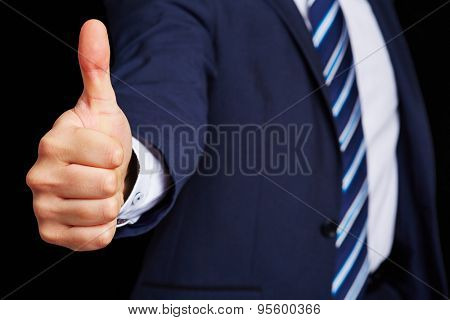 Successful business manager in a suit holding his thumbs up