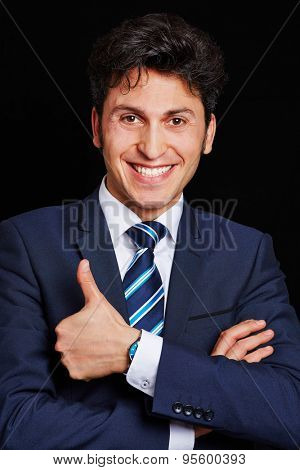 Successful business man holding thumbs up on dark background