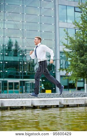 Smiling business man running to appointment in front of office building