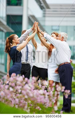 Group of business people giving high five outdoors in front of the office