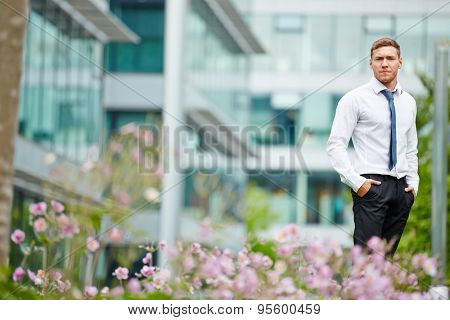 Young business man standing in front of an office and looking serious