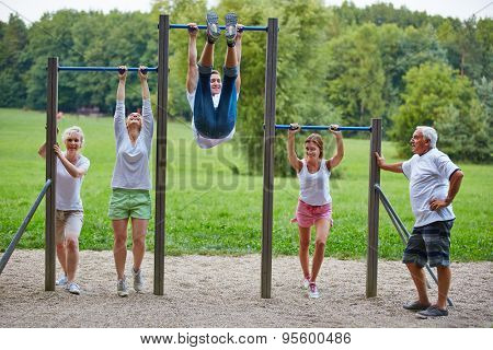 Family doing fitness training together in park at horizontal bars