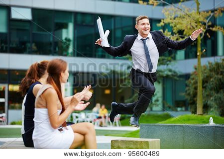 Brave businessman jumping over obstacle in front of his team members