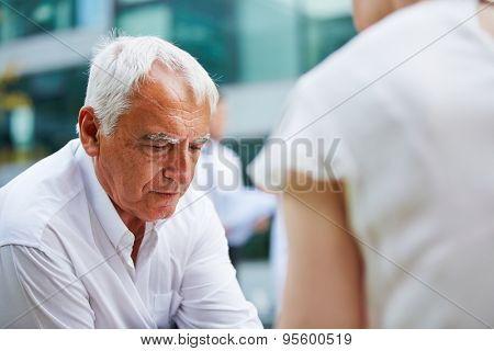 Pensive old business man sitting worried outdoors