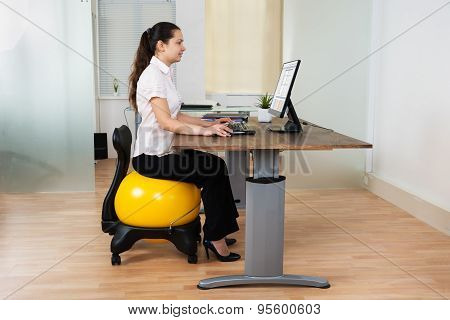 Businesswoman Sitting On Fitness Ball With Computer At Desk