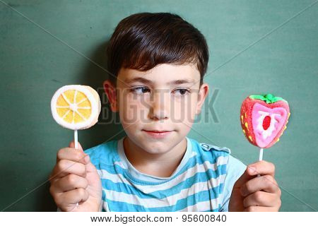 Preteen Handsome Boy With Two Marshmellow Sweets On Stick Isolated On Blue