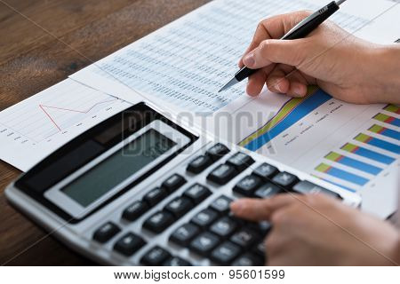 Businesswoman Analyzing Financial Report With Calculator