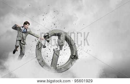 Angry determined businessman crashing stone prohibition symbol
