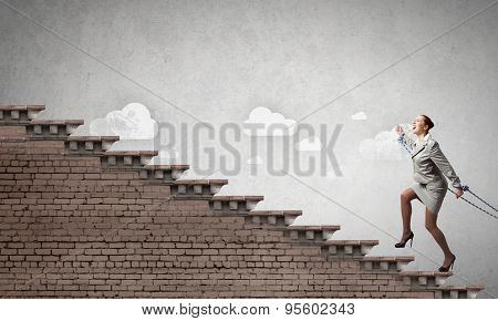 Young businesswoman with ropes on hands climbing ladder