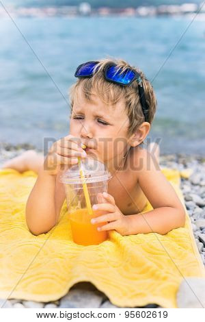 Little Boy Drinks Juice On Beach Against Sea