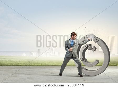 Angry businessman crashing stone trademark with karate kick