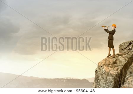 Young woman engineer on rock top looking in spyglass