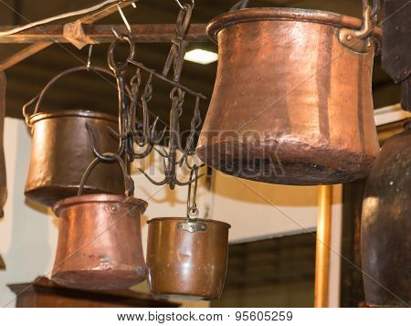 Old Copper Pots Hanged On Iron Hooks
