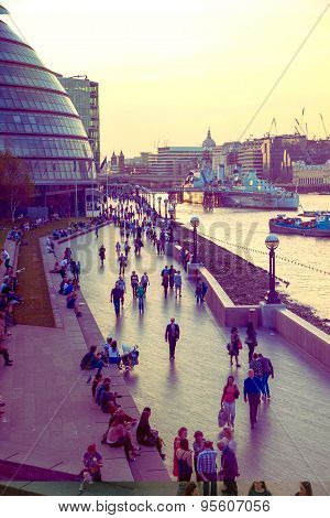 LONDON, UK - APRIL15, 2015: South bank of river Thames in sun set light. View includes a lot of walk