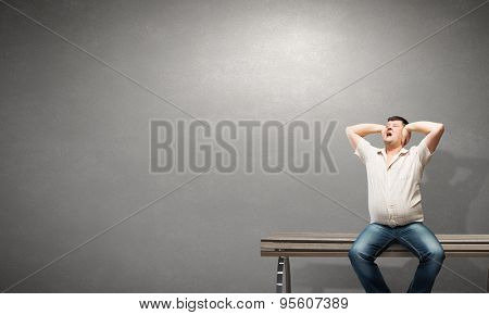 Fat man sitting on bench closing ears with hands