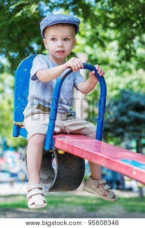 Cute Toddler Boy Riding On A Swing