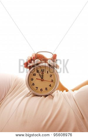 Pregnant Woman With An Alarm Clock On A White Background