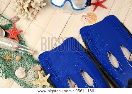 Sea composition with flippers and shells on wooden table close up
