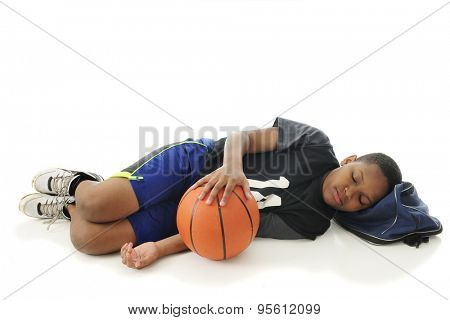 A preteen athlete asleep with his head on his gym bag and hand resting on his basketball.  On a white background with space over the sleeper for your text.
