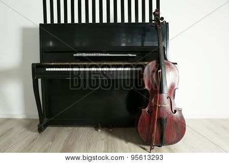 Cello near piano on white wall background