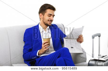 Business man with suitcase sitting on sofa and reading newspaper isolated on white