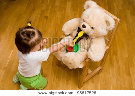 Little Girl Playing With A Toy Bear And Tea Things