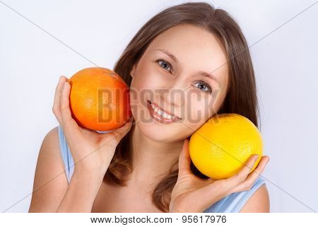 Portrait Of Pretty Young Beautiful Woman With Two Grapefruits In Her Hands. Healthcare. Healthy Life