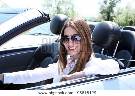 Young girl in cabriolet, outdoors