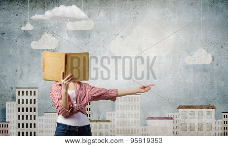 Teenager girl hiding her face behind book
