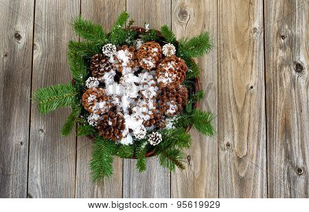 Christmas Basket With Decorations And Snow On Rustic Wooden Boards
