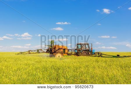 Farming Tractor Spraying Green Field