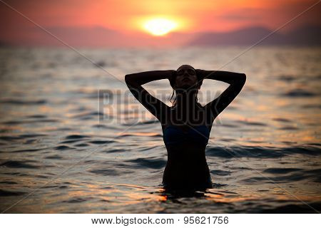 Beautiful woman in water embracing the golden sunshine glow of sunset, enjoying peace, serenity