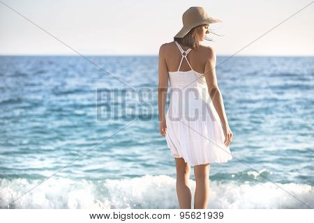 Beautiful woman in a white dress walking on the beach.Relaxed woman breathing fresh air,emotional se