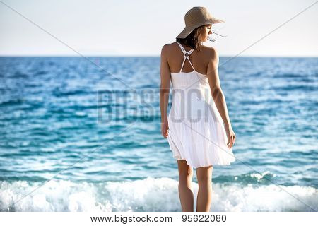Beautiful woman in a white dress walking on the beach.Relaxed woman breathing fresh air,emotional