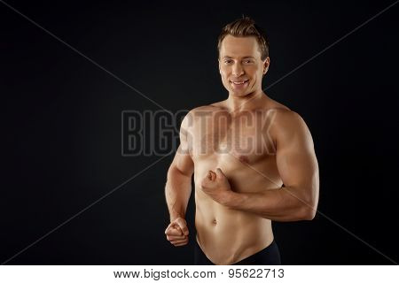 Cheerful young sportsman is flexing his bicep