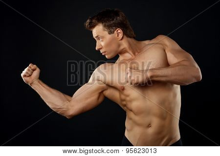 Attractive young sportsman is fighting with someone