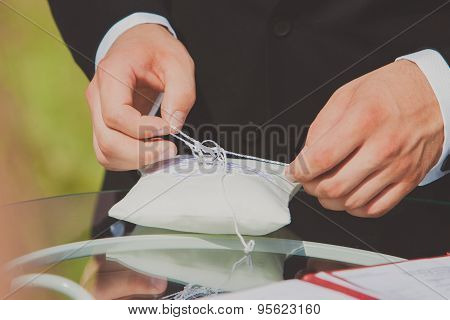 Groom untying ribbon to take wedding ring. Wedding ceremony.