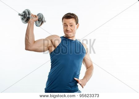 Attractive young male athlete is exercising with iron equipment