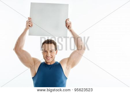 Handsome sportsman is presenting white sheet of paper