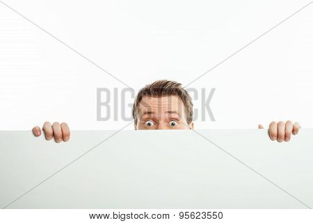 Attractive young man is hiding behind white wall