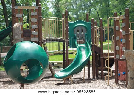 Kids playground with mulch and green slide